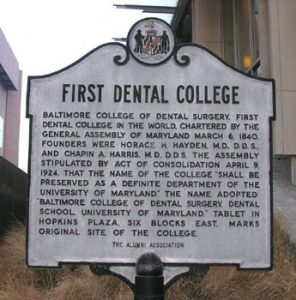 Landmark sign noting the Baltimore College of Dental Surgery as the world's first dental college.